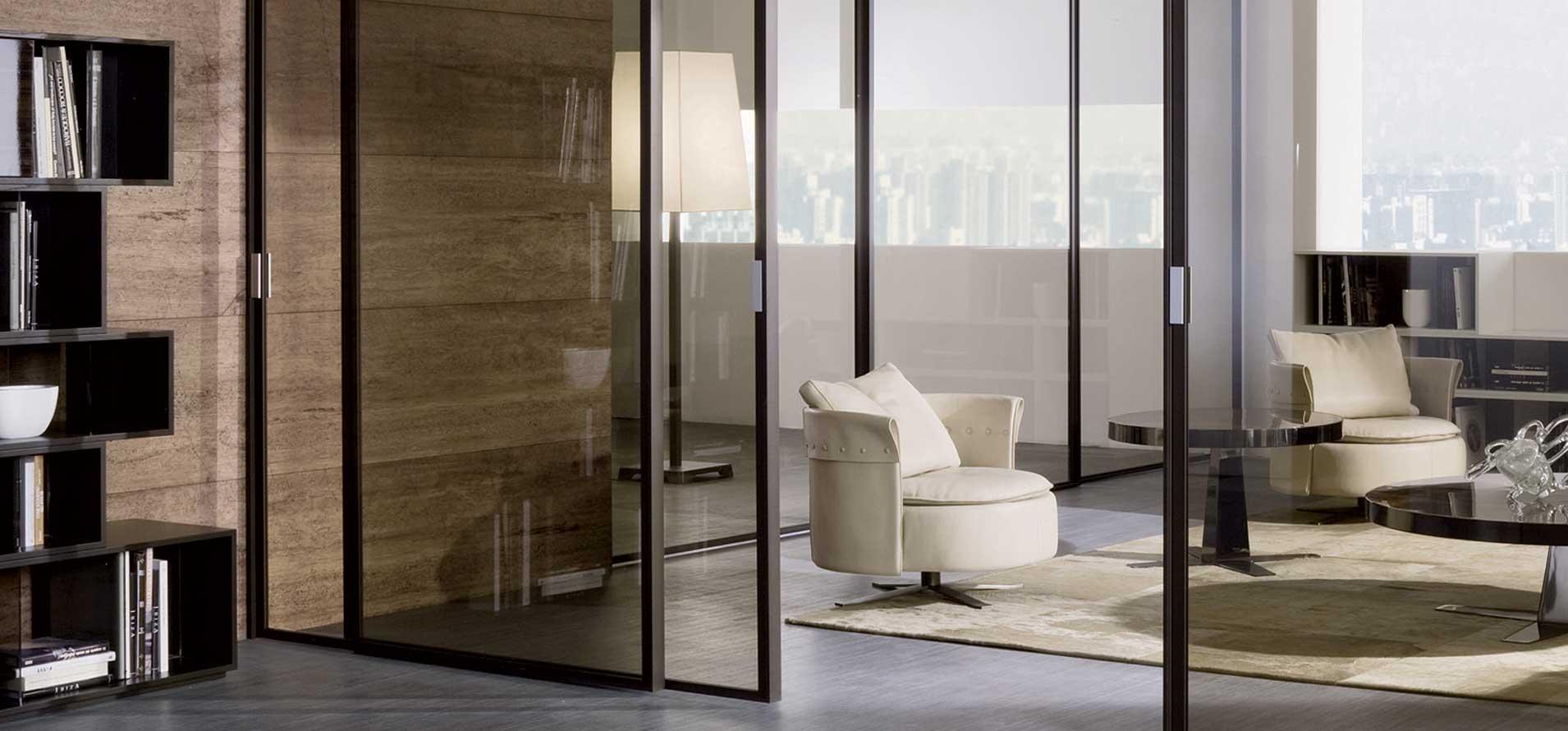 foto a colori, in primo piano la porta scorrevole con il nuovo profilo finitura moka e vetro bronzo che permette di vedere l'ambiente retrostante, un living