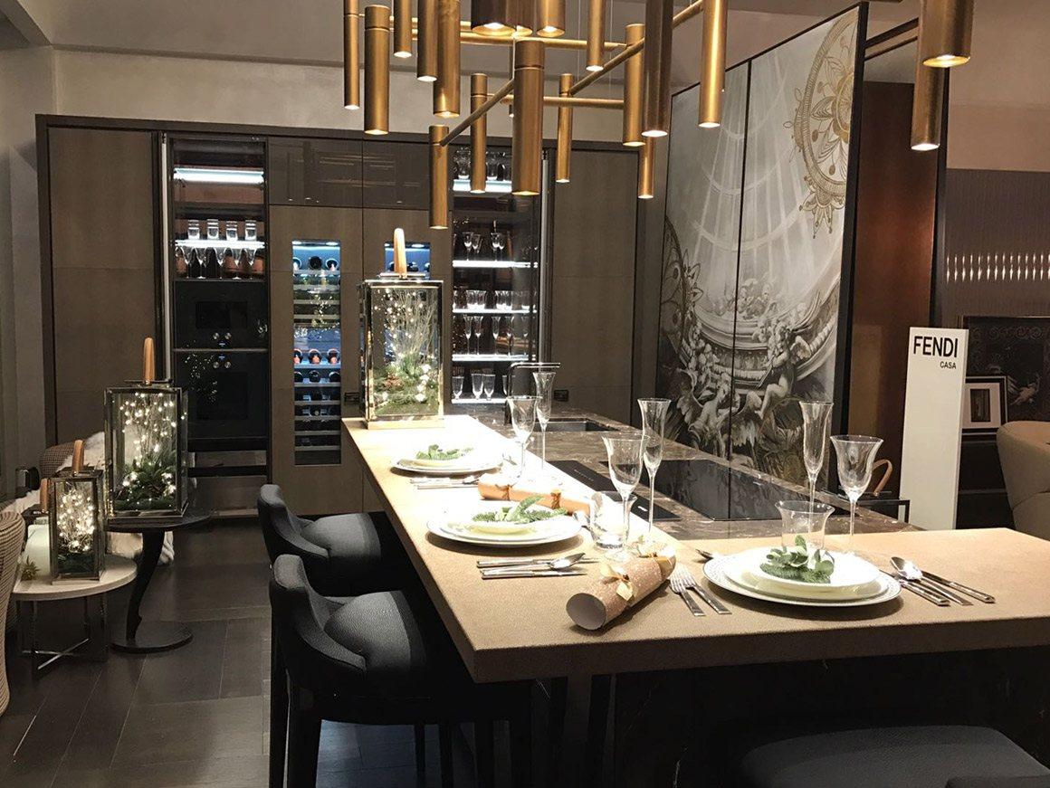 interno showroom a Londra in primo piano l'isola della cucina con snack rivestito in pelle galuchat, l'isola è un monoblocco di marmo. Sullo sfondo le colonne cucina con cantine per vino sulla destra il quadro dell'artista Giovanni Bressana