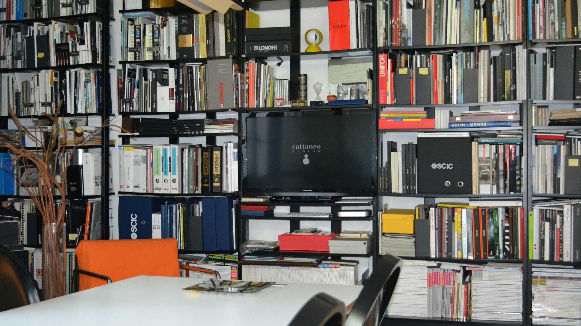 Immagine a colori di un interno dello studio, nella foto è inquadrata la libreria con TV per proiezioni progetti e tutti cataloghi che utilizziamo per progettare, si vedono le ditte con le quali collaboriamo, come SCIC, LONGHI, FLOU, FLEXFORM, PORADA, LEMA, POLIFORM e molte altre.