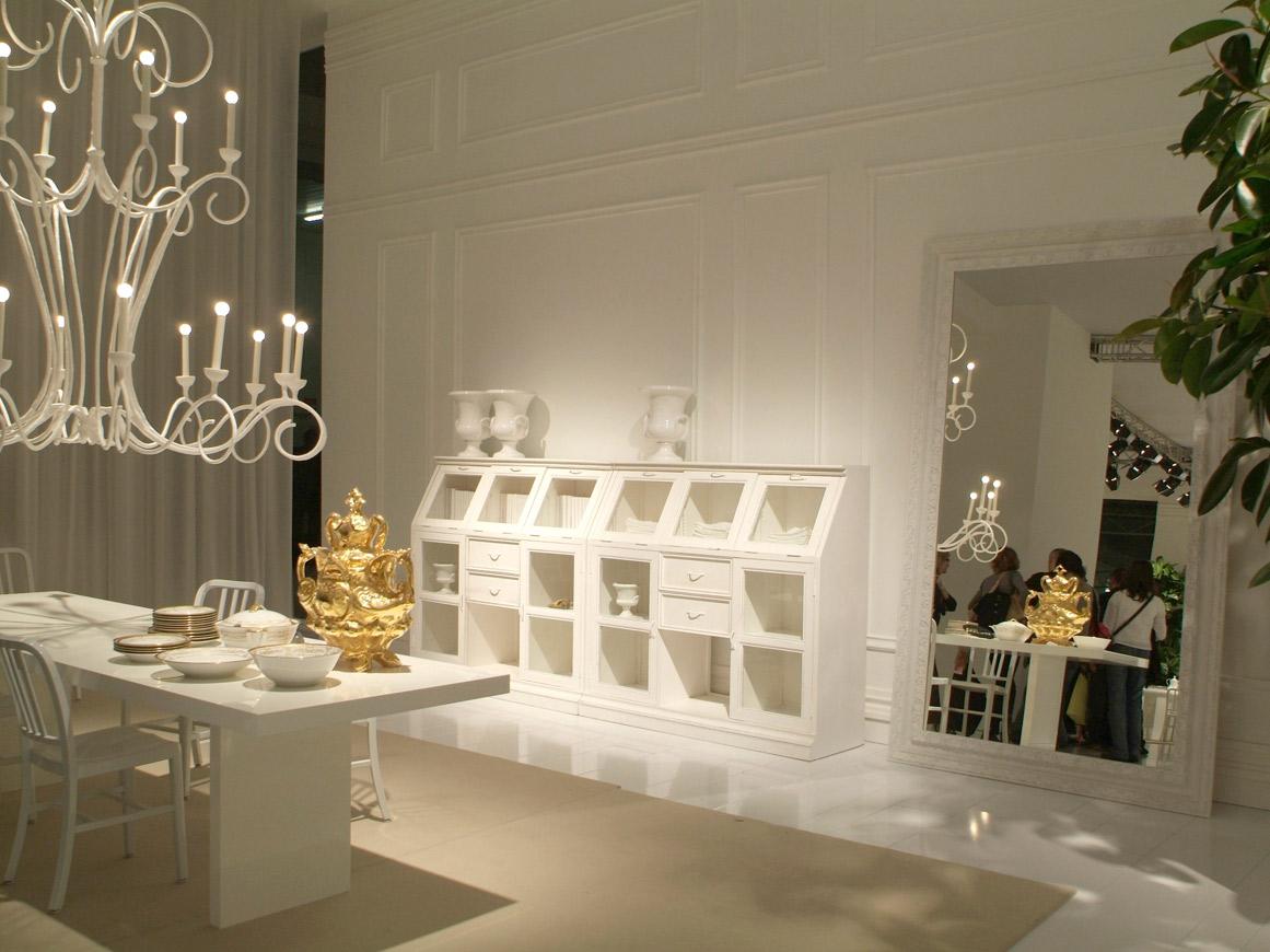 foto interna dello stand con credenza laccata bianca con gioco di pieni e vuoti tra cassetti in legno ed ante in vetro, sulla sinistra tavolo da pianto con grande lampadario scenografico sempre bianco